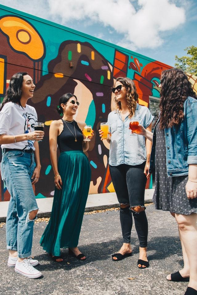 4 modnie ubrane kobiety rozmawiają na ulicy