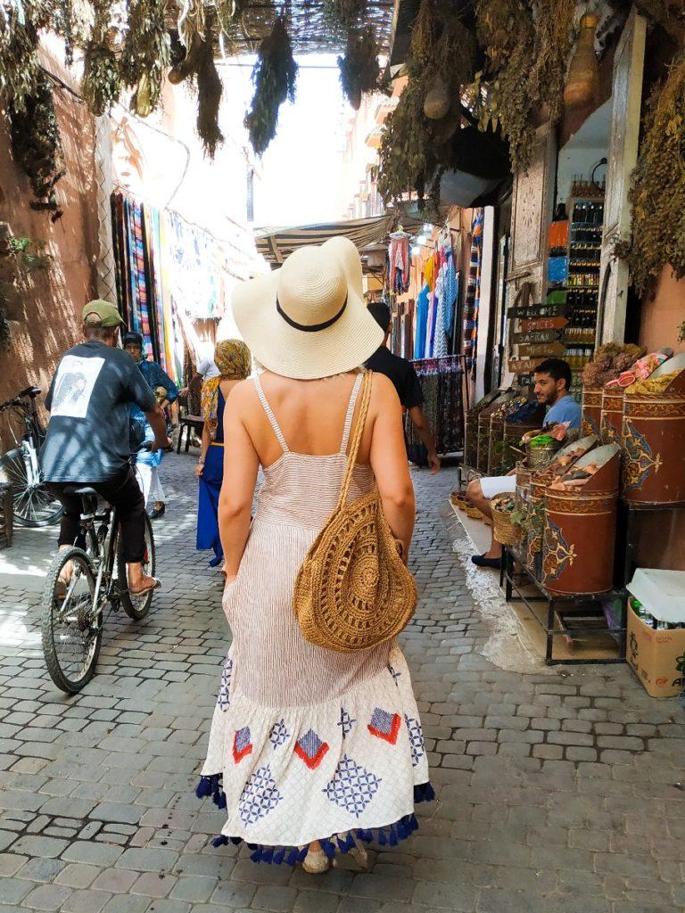 Ubiór w Maroku. Kobieta w boho sukience i kapeluszu w medinie Marrakeszu.