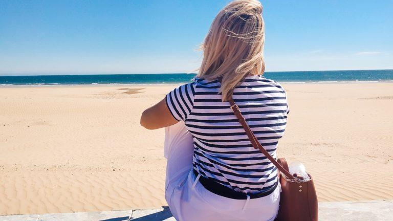 Blondynka w Maroku siedzi odwrócona plecami. Przed sobą ma ocean i plażę. Nosi koszulkę w marynarskie paski i białe spodnie.