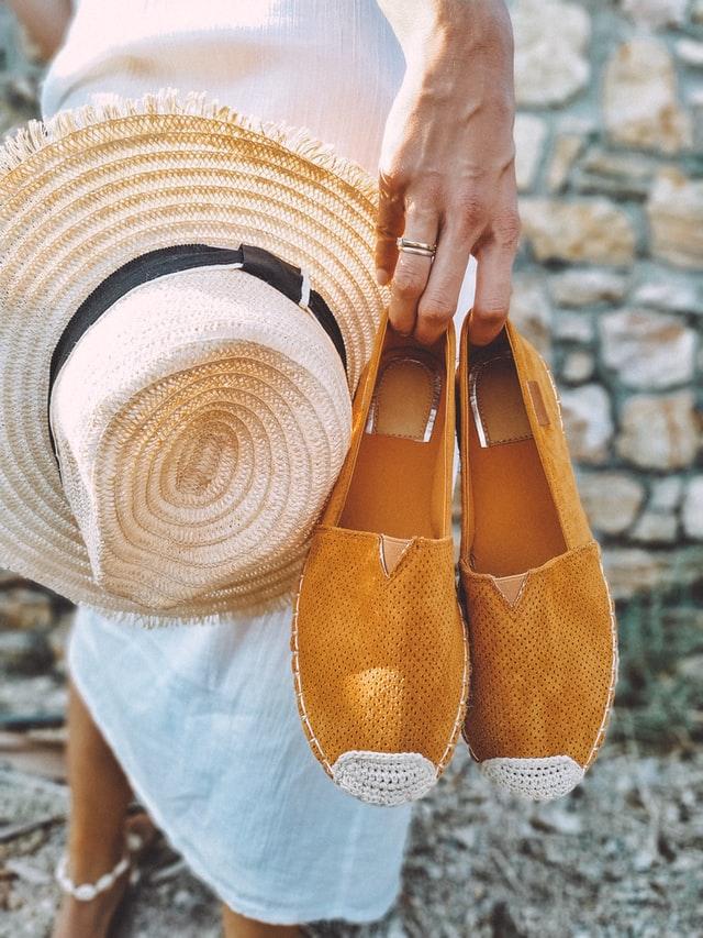tkaniny na lato. Kobieta w białej sukience trzyma w dłoniach kapelusz i espadryle