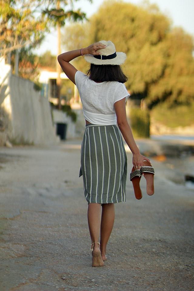 Kobieta ubrana w białą bluzkę i spódnicę w paski spaceruje, trzymając w rękach klapki.