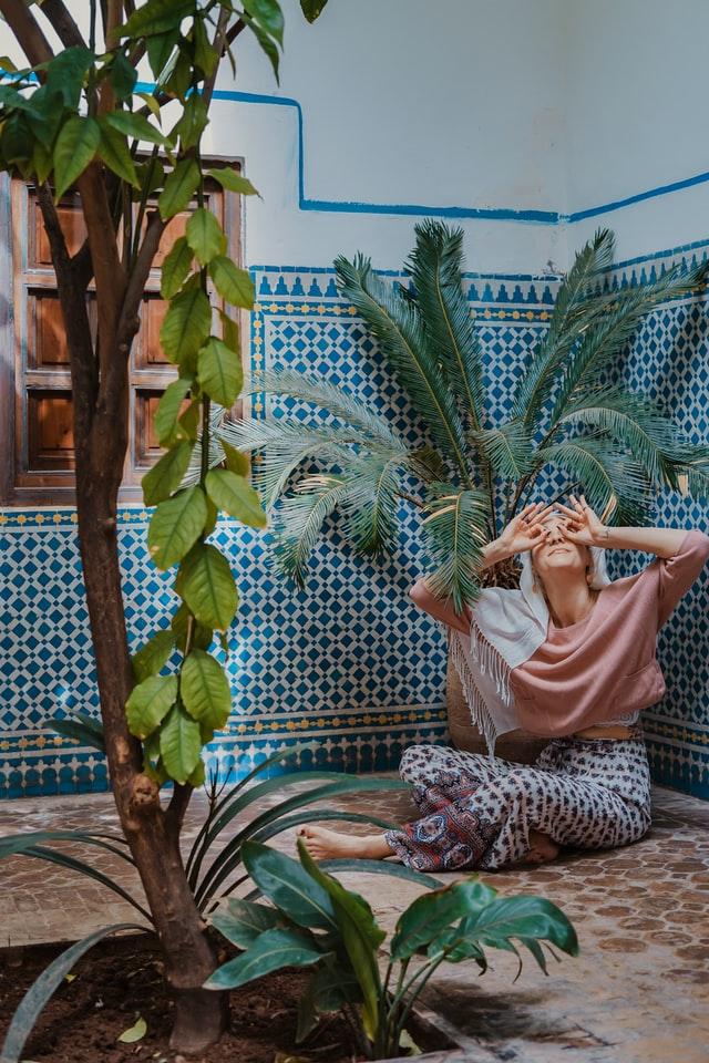 Kobieta w boho stroju siedzi na podłodze riadu w Maroku
