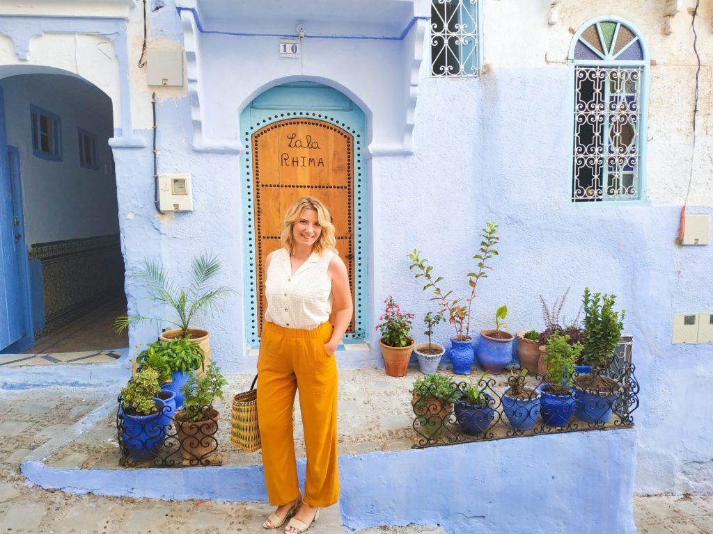 Kobieta w Chefchaouen na tle niebieskich budynków i drzwi