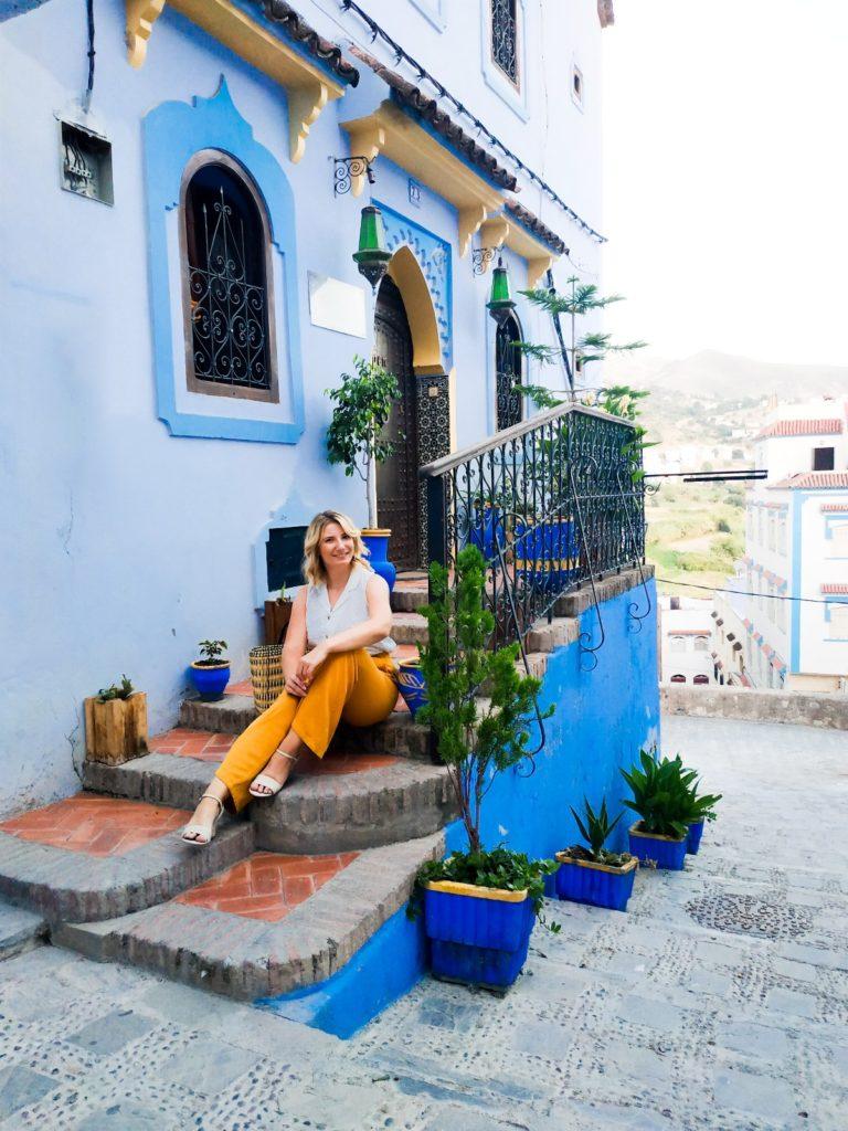 Kobieta siedzi na schodach niebieskiego budynku w Chefchaouen