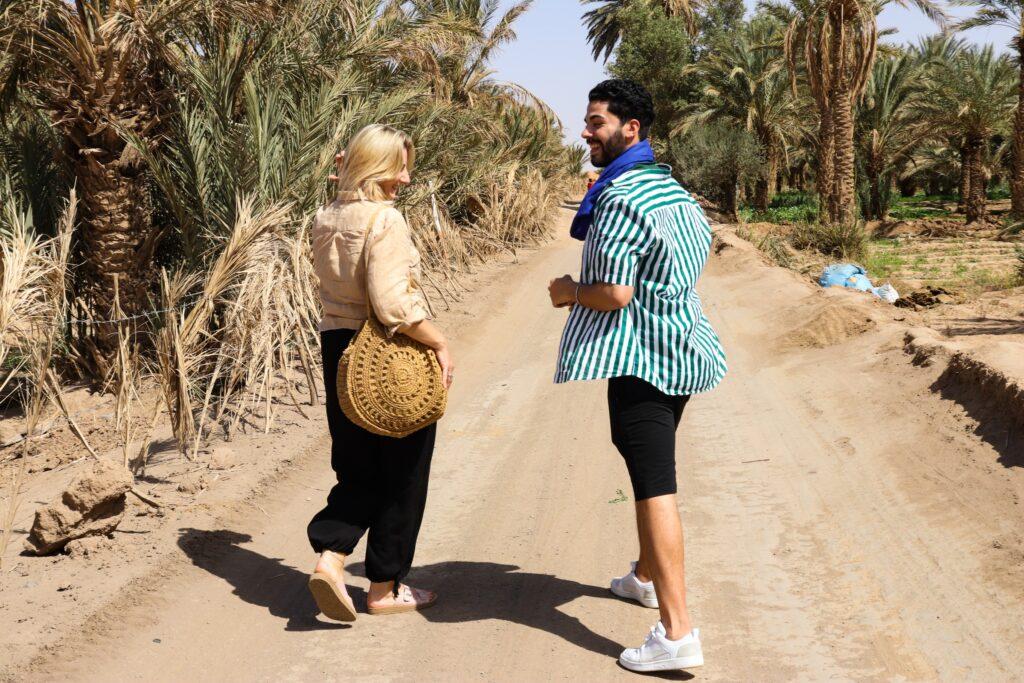 kobieta i mężczyzna para spaceruje wśród palm, śmiejąc się